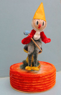 22b: An elf sitting on a mushroom is about 19cm high. No indication of origin. All different colored chenille; the inside of the box is plain cardboard.