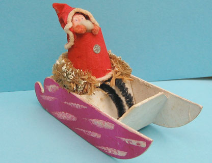 31b: Japanese Santa in sleigh, plaster face, chenille arms and legs, paper hood/coat,