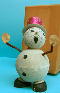 "34: 19cm high snowman container with hands mounted on springs. The head comes off at the neck, revealing the container. Possibly with its original box, although it seems too small; on the side is stamped '7020' and '24' and in pencil ""Blanc"" (white)"