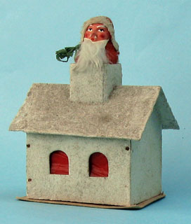 60: Santa, plaster face, rabbit fur beard, paper tree, in the chimney of a wooden house, covered with glitter, candy container, walls are of wood, roof and base of cardboard, 9cm x 13cm high