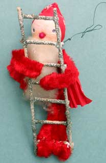 Santa with possibly cotton face; cardboard ladder and crèpe hooded cape.