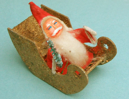 Santa with a paper face in a gold-glitter sledge.