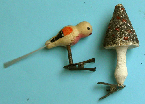 Two ornaments on a clip, a bird with glass tail and a mushroom, both with a different design clip.