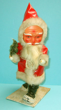 PL2: Santa with hard plastic face and body; eyes are not painted but printed paper; beard is rabbit fir; red plastic coat; height is about 28 cm.